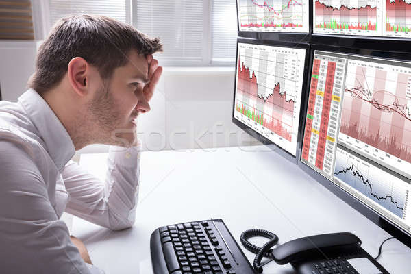 Sad Male Operator Looking At Graphs On Multiple Computer Screen Stock photo © AndreyPopov
