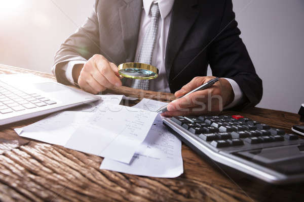 Businessperson Looking At Receipts Through Magnifying Glass Stock photo © AndreyPopov