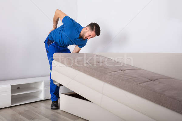 Mover Suffering From Backpain While Lifting Sofa Stock photo © AndreyPopov