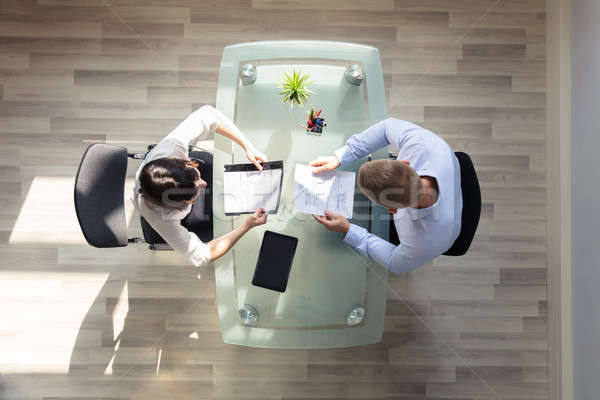 Elevated View Of Two Businesspeople Holding Resume Stock photo © AndreyPopov