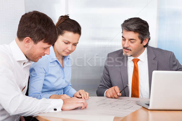 Broker Explaining To Young Couple Stock photo © AndreyPopov
