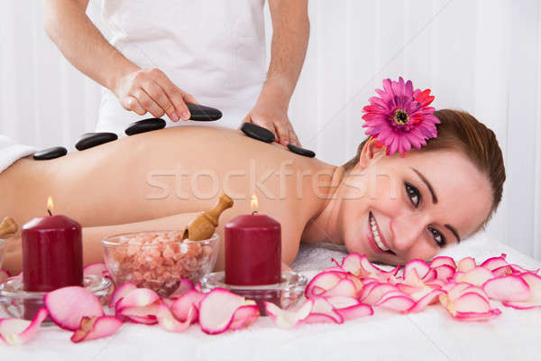 Happy woman getting hot stone therapy Stock photo © AndreyPopov
