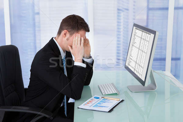 Businessman Suffering From Headache At Computer Desk Stock photo © AndreyPopov