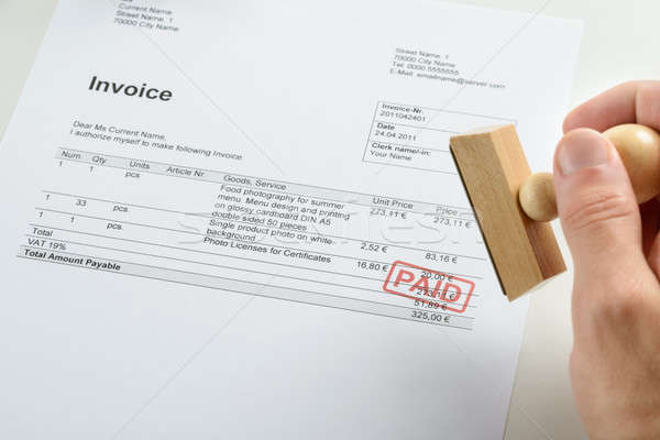 Person Hand Holding Rubber Stamp Over Paid Invoice Stock photo © AndreyPopov