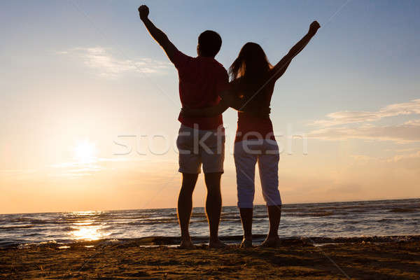 Couple With Hands Raised At Beach During Sunset Stock photo © AndreyPopov