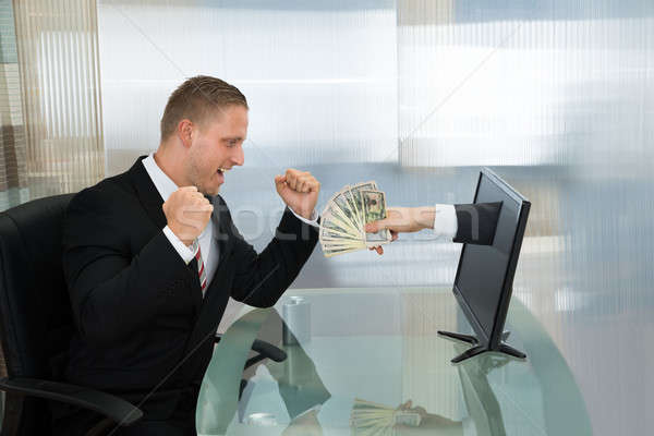 Excited Businessman With Money Coming Out From Computer Screen Stock photo © AndreyPopov