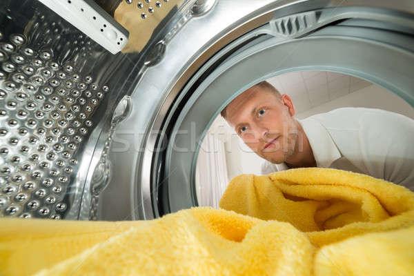 Adam havlu görmek içinde çamaşır makinesi genç Stok fotoğraf © AndreyPopov