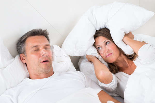 Stock photo: Angry Woman Trying To Sleep With Snoring Man