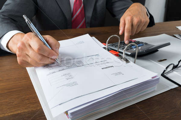 Businessman Checking Receipts At Desk Stock photo © AndreyPopov