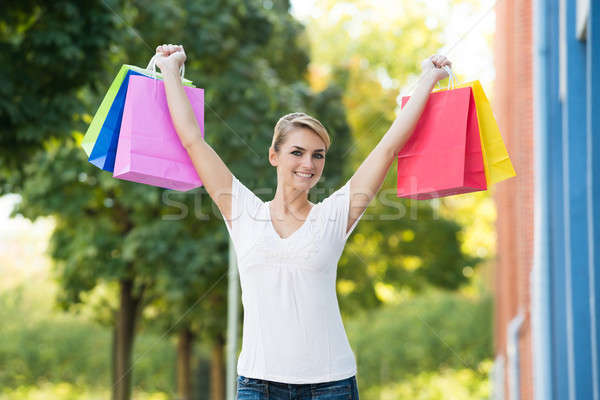 Woman With Arms Raised Carrying Shopping Bags Stock photo © AndreyPopov