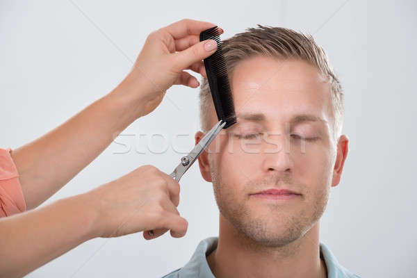 Young Man Getting His Eyebrow Trimmed Stock photo © AndreyPopov