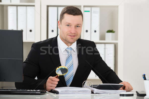 Accountant Analyzing Invoice With Magnifying Glass Stock photo © AndreyPopov