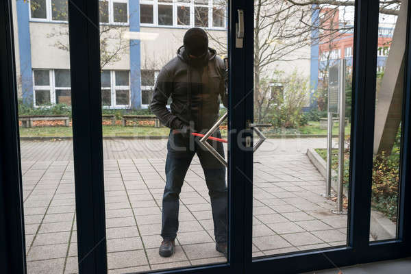 Hooded Man Using Crowbar To Open Glass Door Stock photo © AndreyPopov