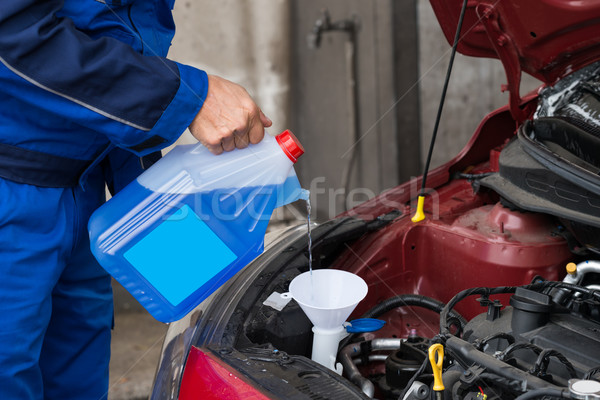 Serviceman Pouring Windshield Washer Fluid Into Car Stock photo © AndreyPopov