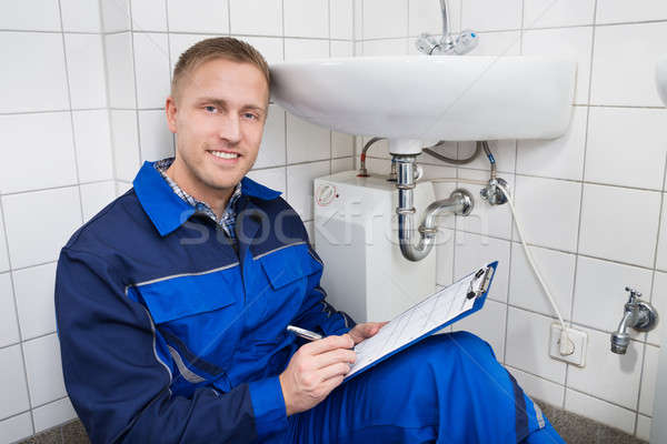 Young Plumber Writing On Clipboard Stock photo © AndreyPopov