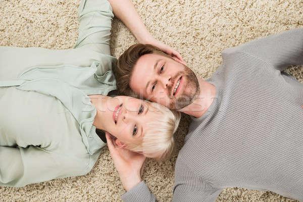 Happy Couple Lying On Carpet Stock photo © AndreyPopov