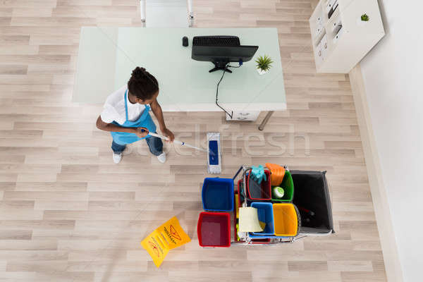 Young Female Janitor Mopping Wooden Floor Stock photo © AndreyPopov