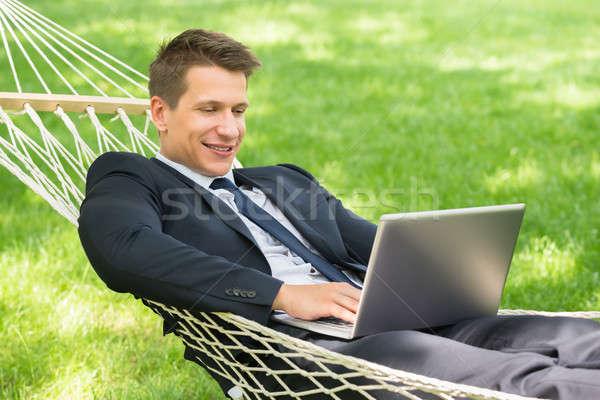 Férfi függőágy laptopot használ boldog fiatalember technológia Stock fotó © AndreyPopov