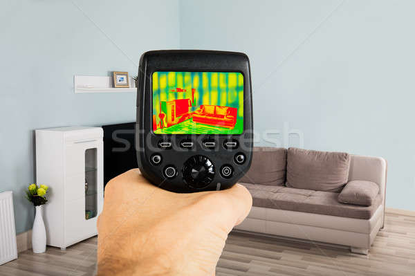 Person Hand Using Infrared Thermal Camera In Living Room Stock photo © AndreyPopov