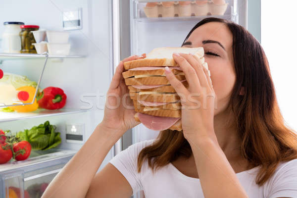 Woman Eating Sandwich In Front Of Refrigerator Stock photo © AndreyPopov