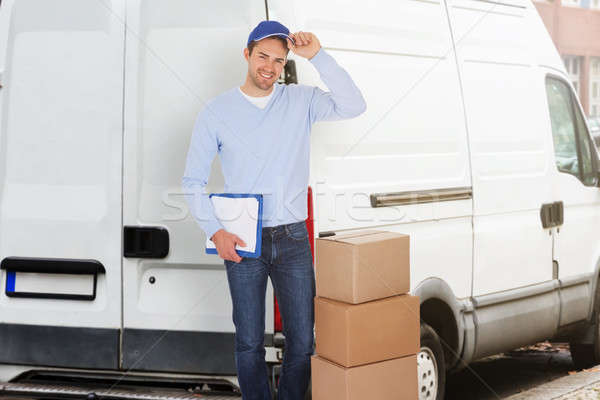 Confident Delivery Man With Parcels And Clipboard Stock photo © AndreyPopov