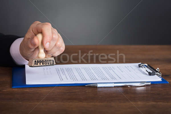 Person's Hand Stamping On Approved Contract Stock photo © AndreyPopov