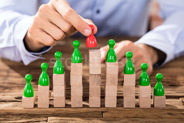 Person Placing Red Figure On Stacked Blocks Stock photo © AndreyPopov