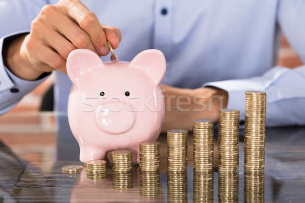 Businessman Insert Coins In Piggy Bank Stock photo © AndreyPopov