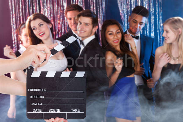 Hands Holding Clapperboard While Friends Dancing In Nightclub Stock photo © AndreyPopov