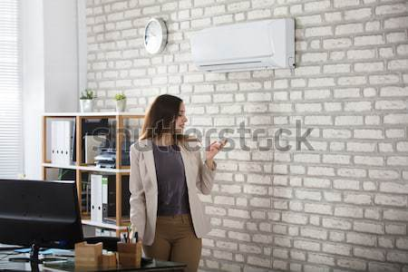 Businesswoman Using Remote Control Of Air Conditioner Stock photo © AndreyPopov