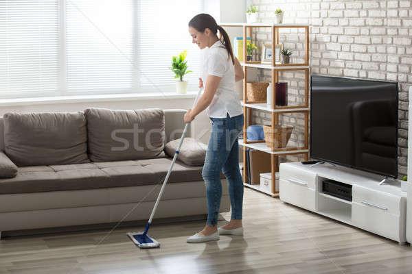 Fiatal nő takarítás keményfa padló boldog nappali nő Stock fotó © AndreyPopov