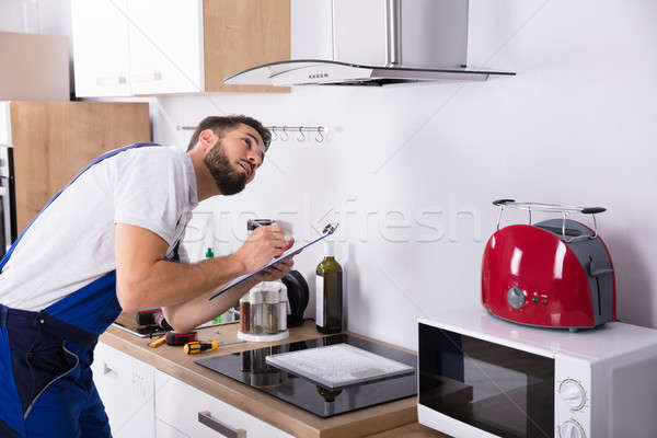 Technician Writing On Clipboard In Front Of Kitchen Extractor Stock photo © AndreyPopov
