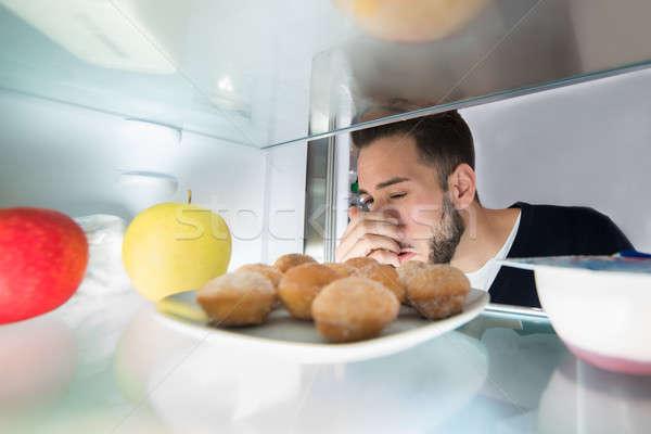 Homme nez alimentaire réfrigérateur Photo stock © AndreyPopov