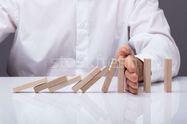 Human Hand Stopping Wooden Blocks From Falling Stock photo © AndreyPopov