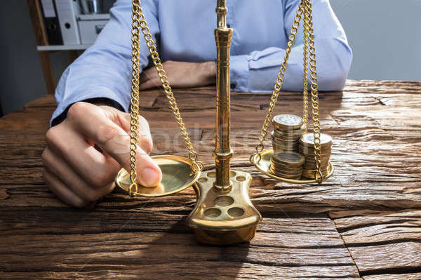 Businessperson Balancing Coins On Justice Scale With His Finger Stock photo © AndreyPopov