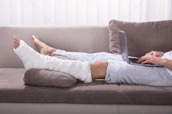 человека сломанной ногой используя ноутбук сидят диван дома Сток-фото © AndreyPopov