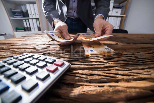 Businessperson's Hand Counting Banknotes Stock photo © AndreyPopov