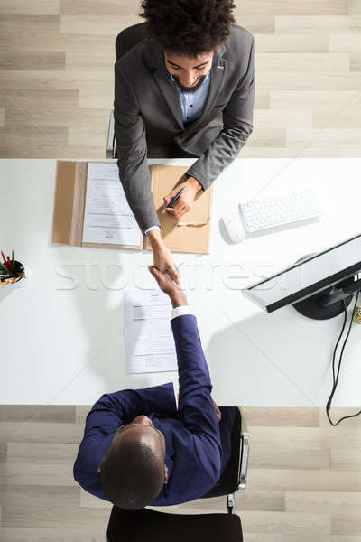 Young Businessman Shaking Hand With Candidate Over White Desk Stock photo © AndreyPopov