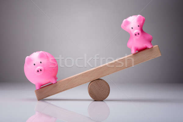 Unbalance Of Two Piggybanks On Wooden Seesaw Stock photo © AndreyPopov