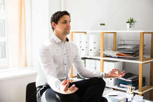 Businessman meditating in lotus position Stock photo © AndreyPopov