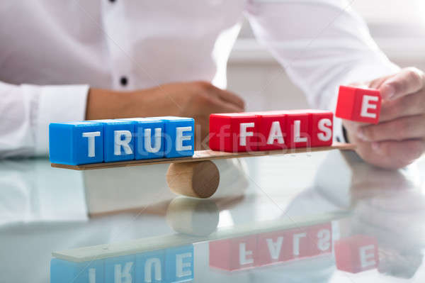 Businessman balancing true and false blocks on seesaw Stock photo © AndreyPopov