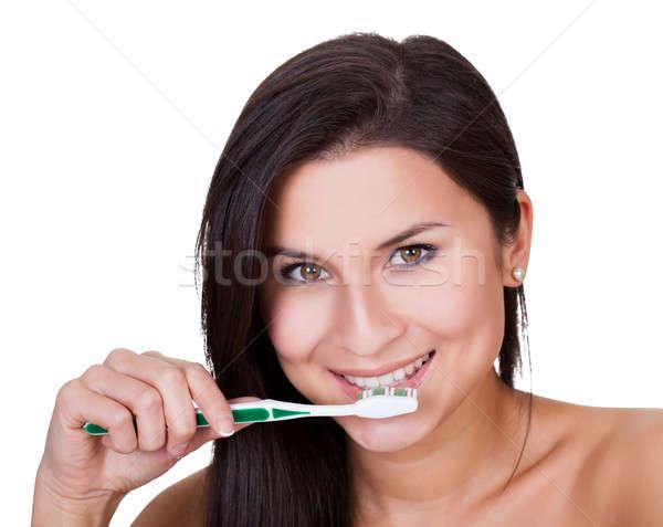 Beautiful woman brushing her teeth Stock photo © AndreyPopov