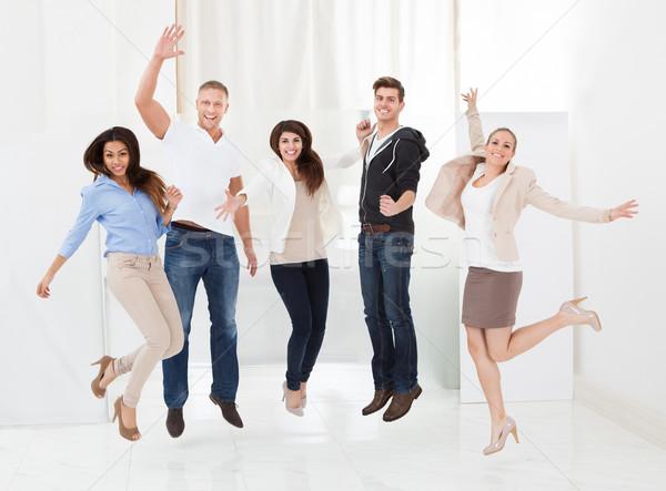 üzletemberek ugrik karok a magasban teljes alakos portré iroda Stock fotó © AndreyPopov