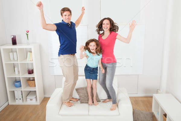 Portrait Of Excited Family Jumping On Sofa Stock photo © AndreyPopov