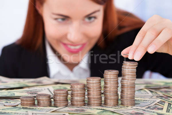 Businesswoman Stacking Coins As Bar Graph Stock photo © AndreyPopov