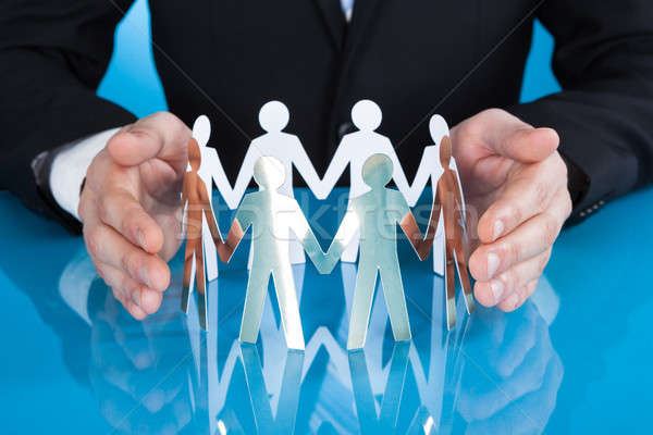 Businessman's Hands Protecting Team Of Paper People On Desk Stock photo © AndreyPopov
