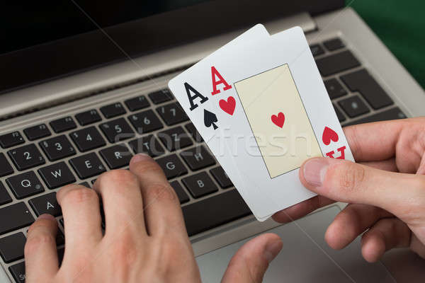 Businessman Holding Cards While Using Laptop Stock photo © AndreyPopov