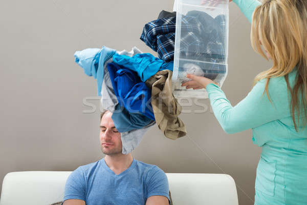 Woman Throwing Laundry On Husband Stock photo © AndreyPopov