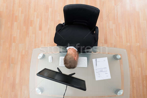 Businessman Leaning On Computer Keyboard Stock photo © AndreyPopov