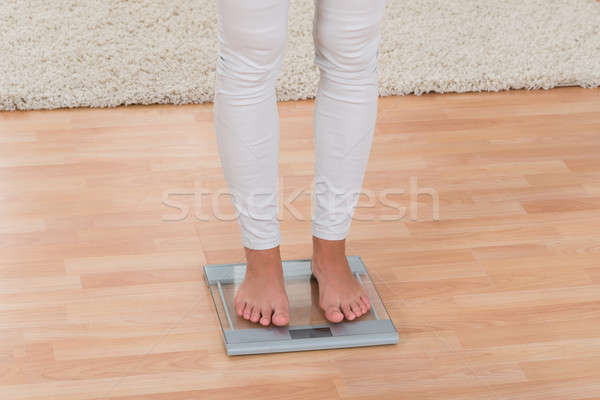 Woman Standing On Weighing Scale Stock photo © AndreyPopov